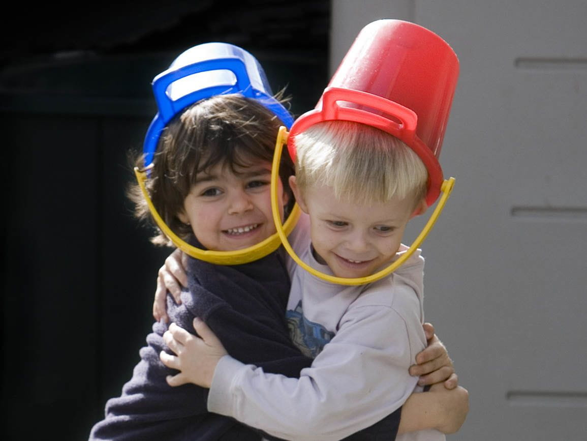 Two friends playing with buckets on their heads