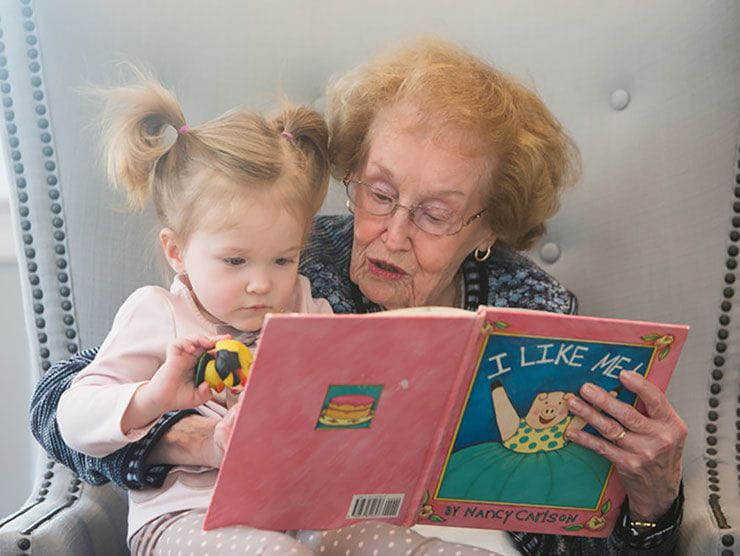Grandmother reading to her toddler granddaughter