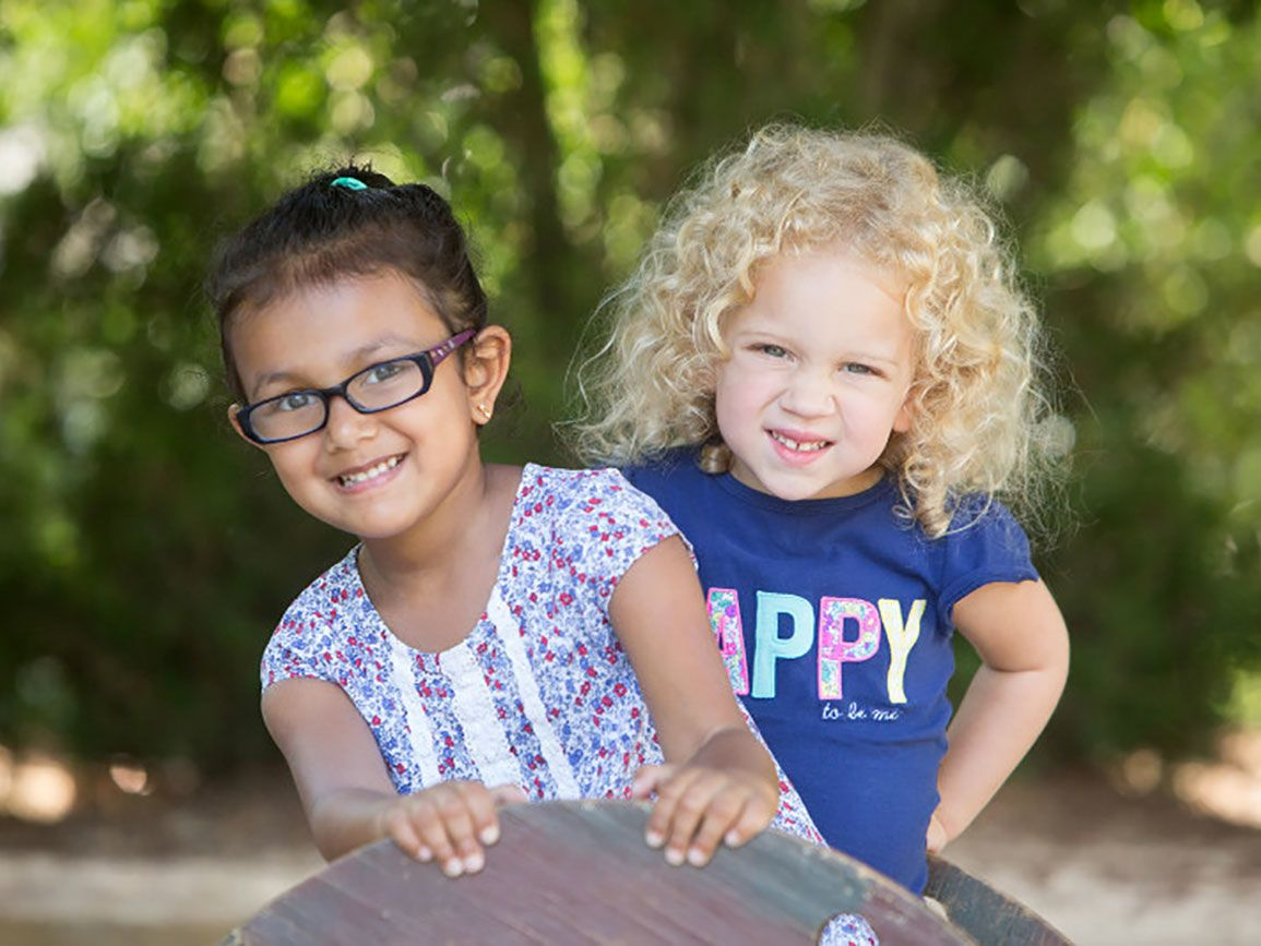 Two preschool girls smiling outside at summer camp