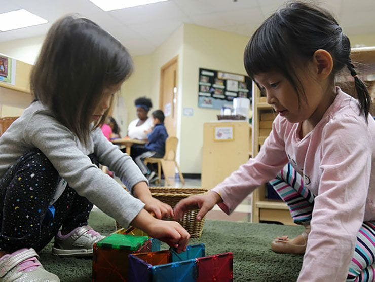 Two preschool girls working together to build a structure