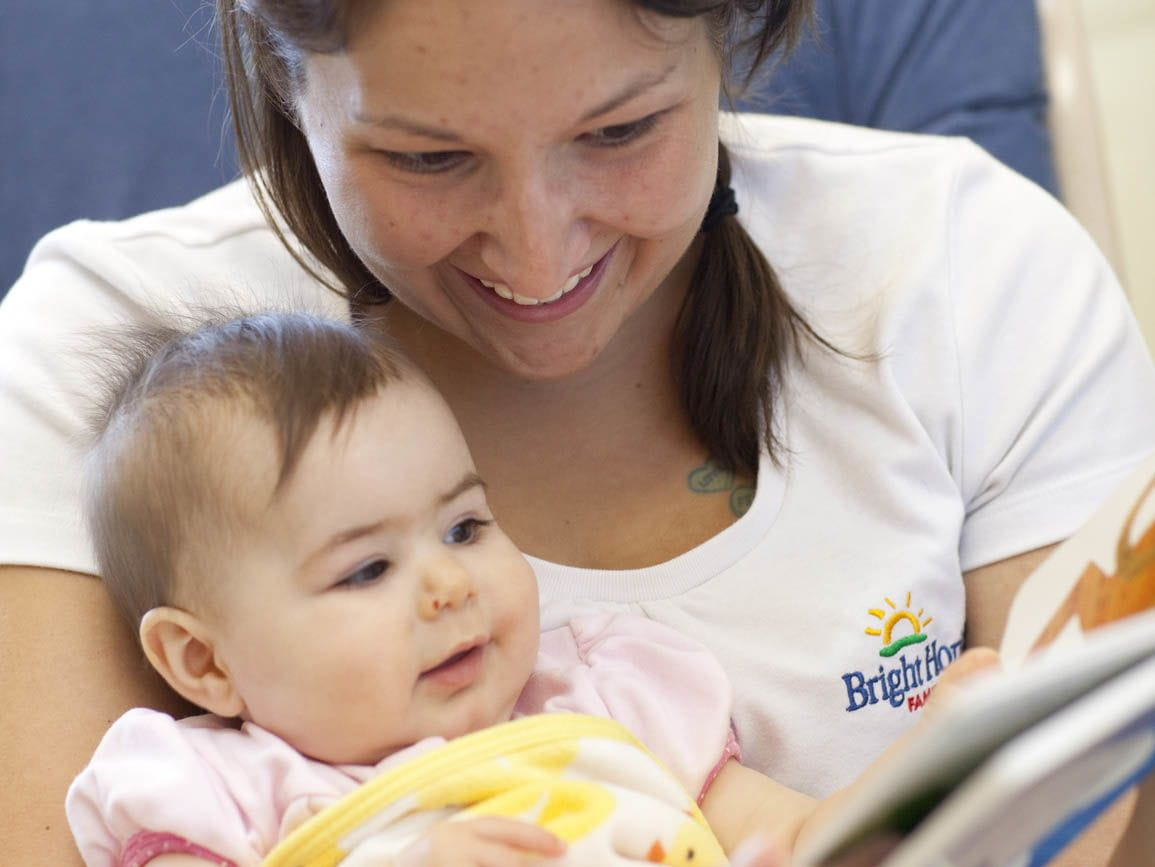 A Bright Horizons child care teacher reading to a baby