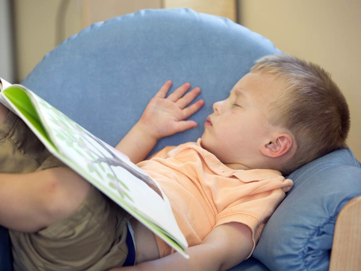 A child napping with a book on his lap