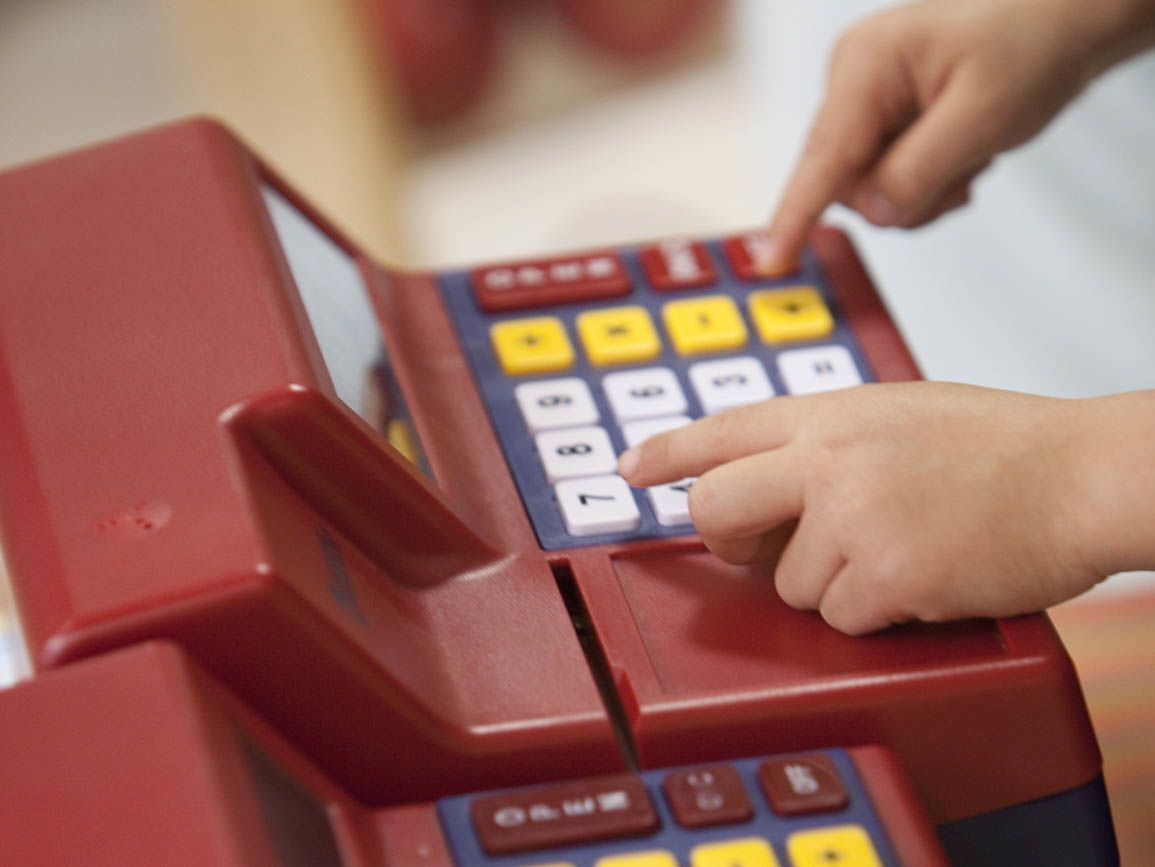 Kid's fingers on a cash register