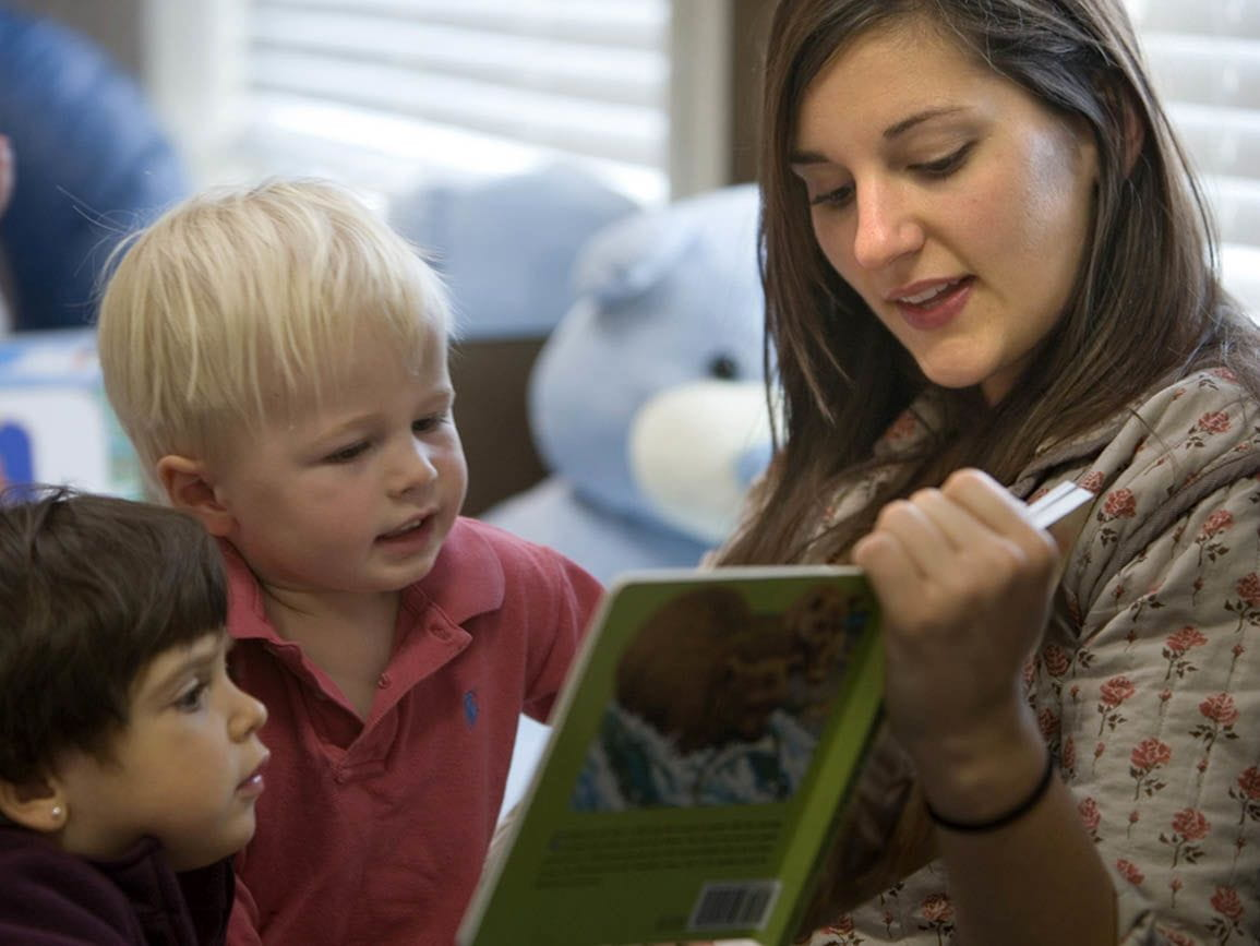 Teacher reading book to toddlers
