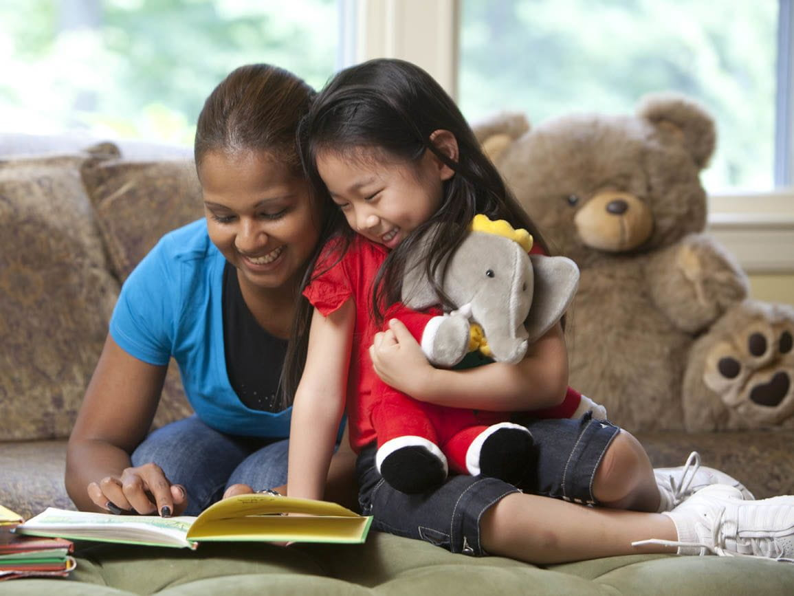 A little girl and a child care teacher reading together