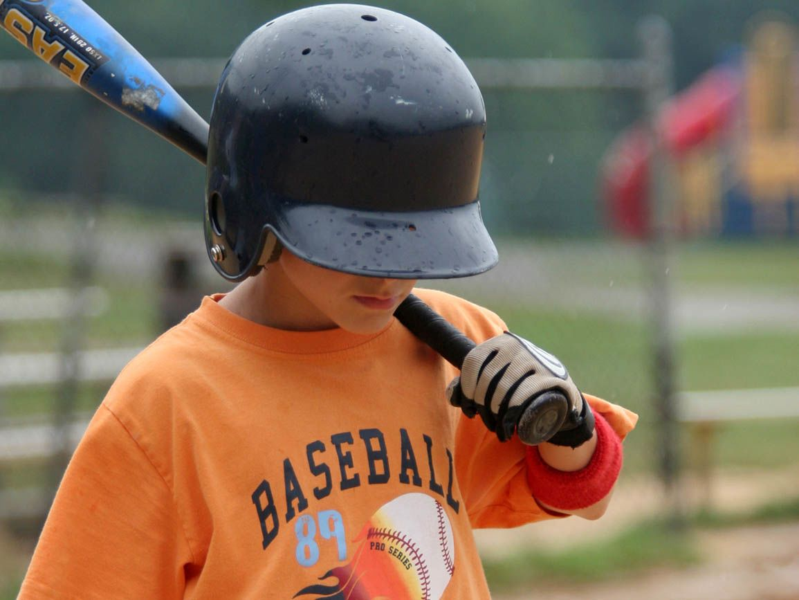 A child in a baseball uniform stepping up to the batter's box