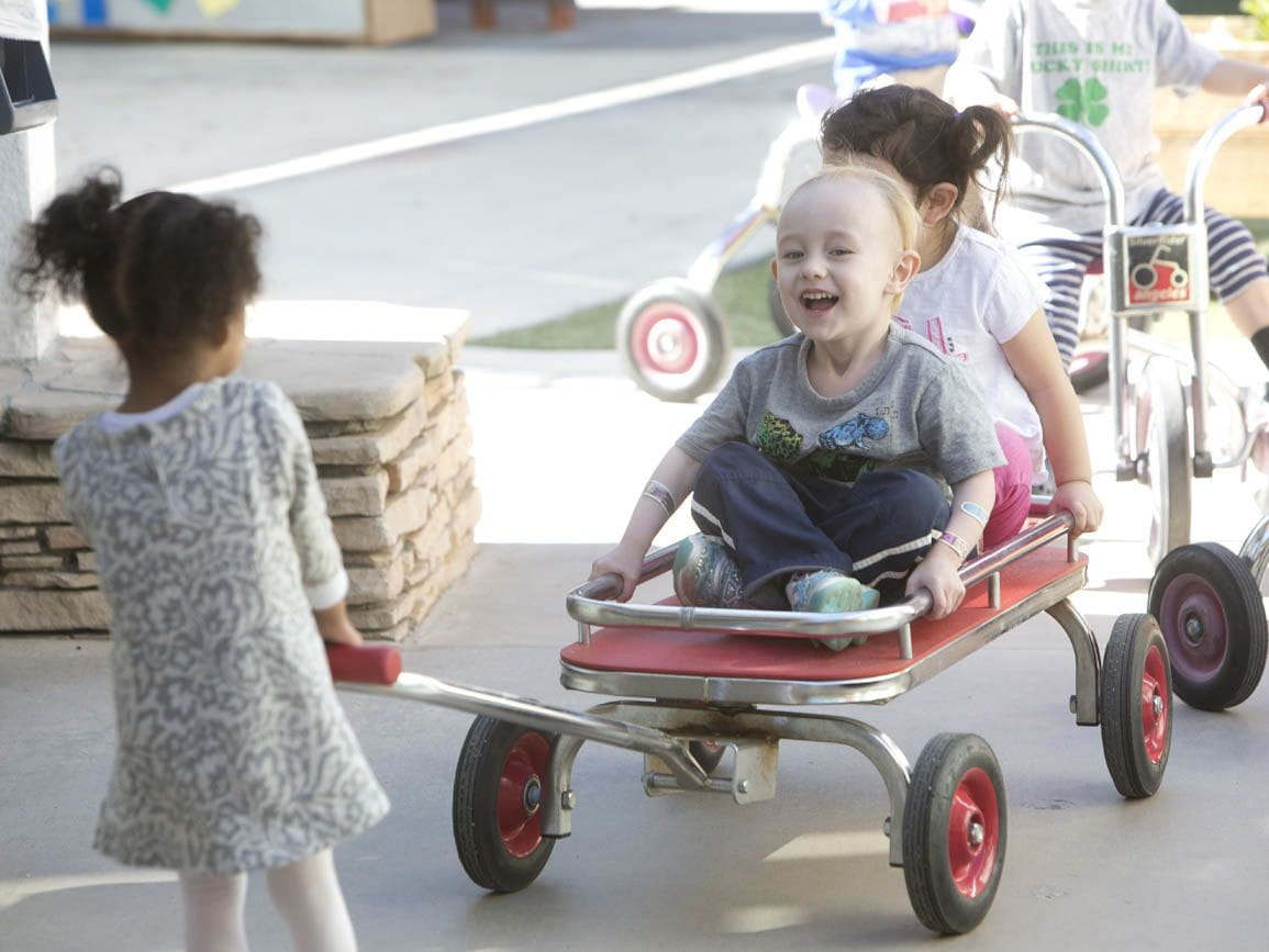 A child pulling two others in a wagon