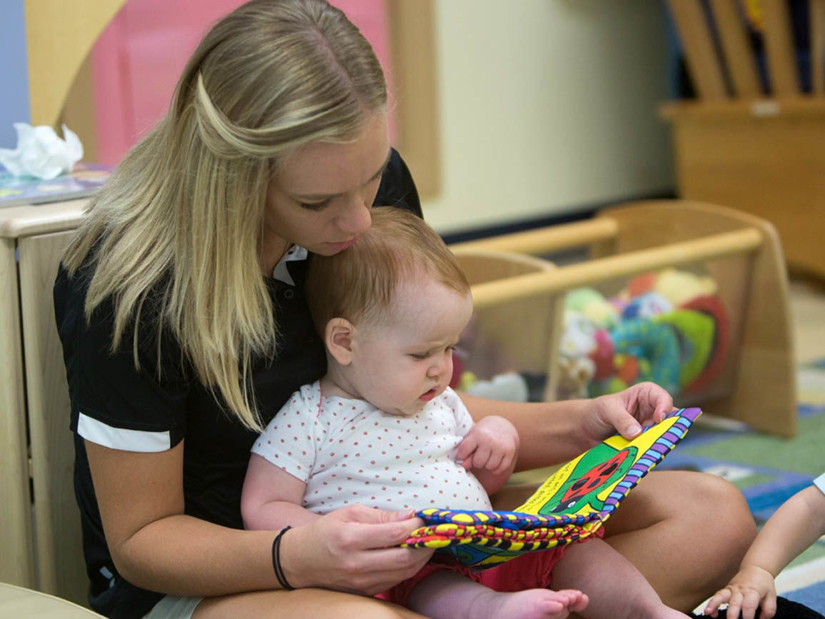 A child care teacher reading to an infant