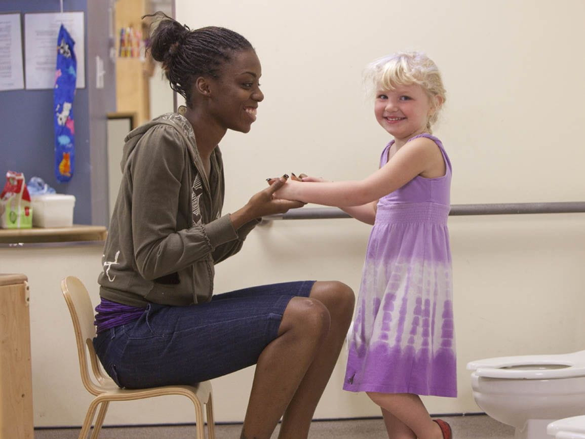 A child care teacher helping a student with potty training