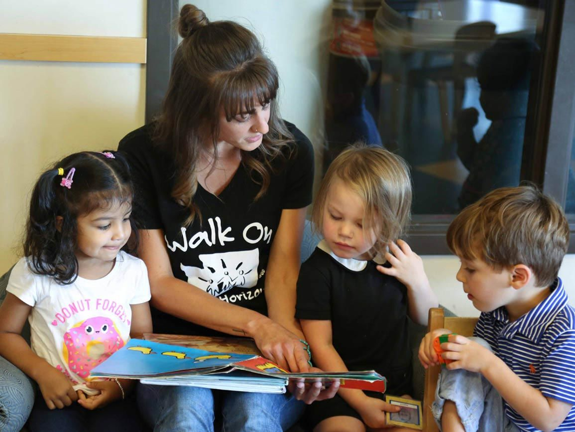A group of children reading with their child care teacher