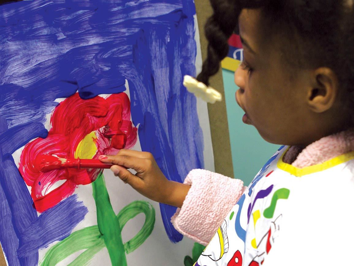 Preschool girl painting a flower at an easel