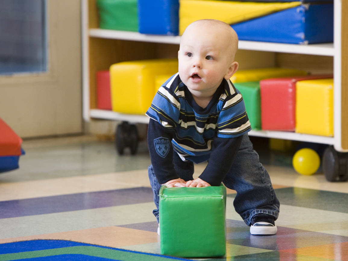 Toddler boy pushing soft green block in gym