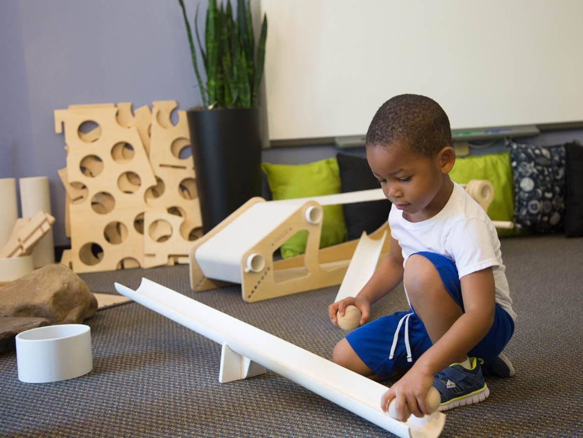 Kindergarten-aged boy building a ramp