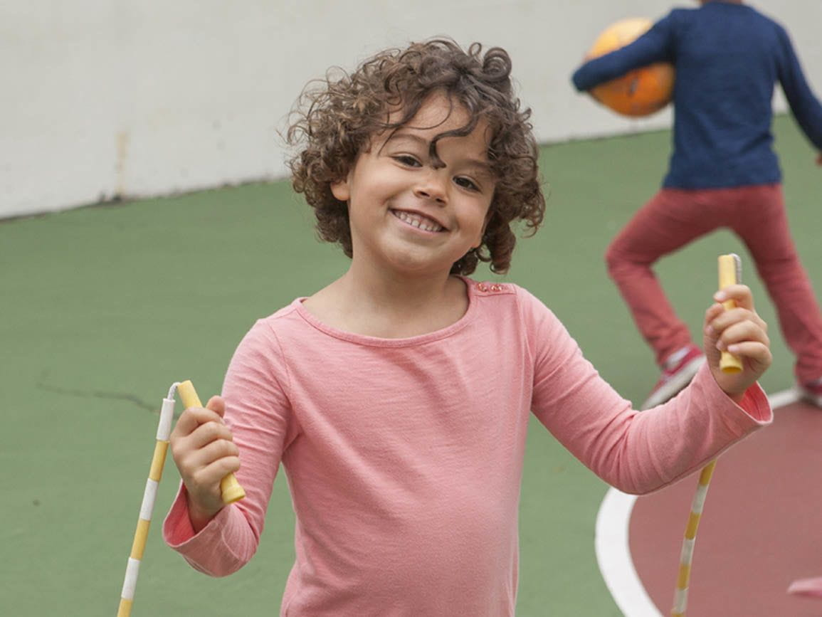 Kindergarten-aged girl using a jump rope at the playground