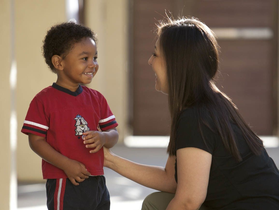 Preschool boy smiling at woman