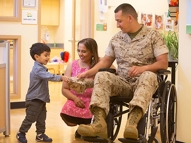 Young boy shaking hands with a wheelchair-bound veteran