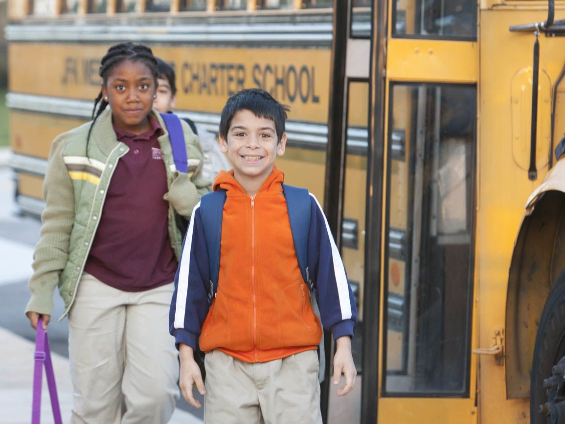 Elementary school-aged boy and girl at school bus
