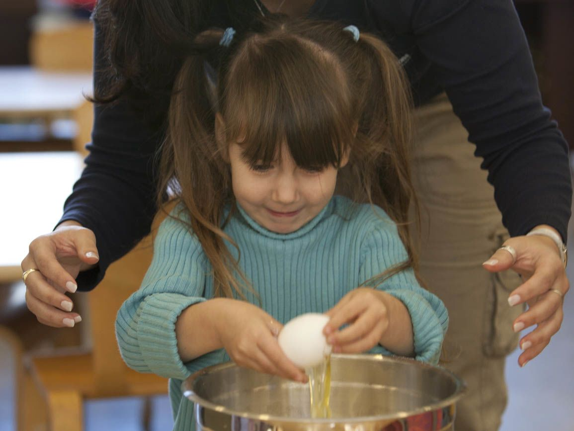 a child cracking an egg