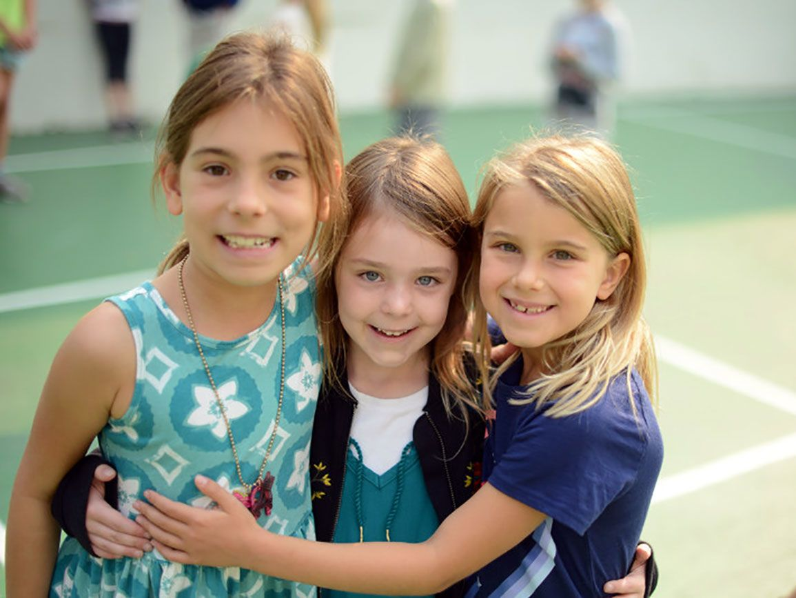 Three school-aged girls arm-in-arm on the playground