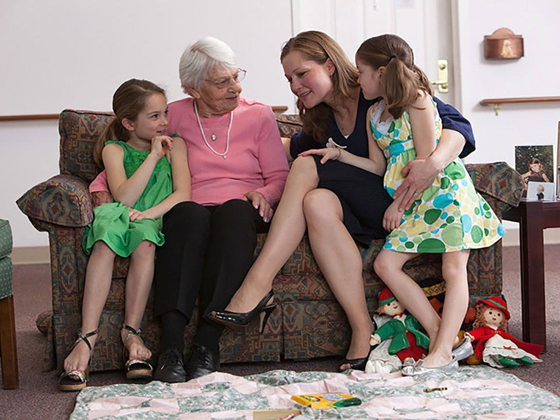 Grandma, mom, and two daughters together on the couch