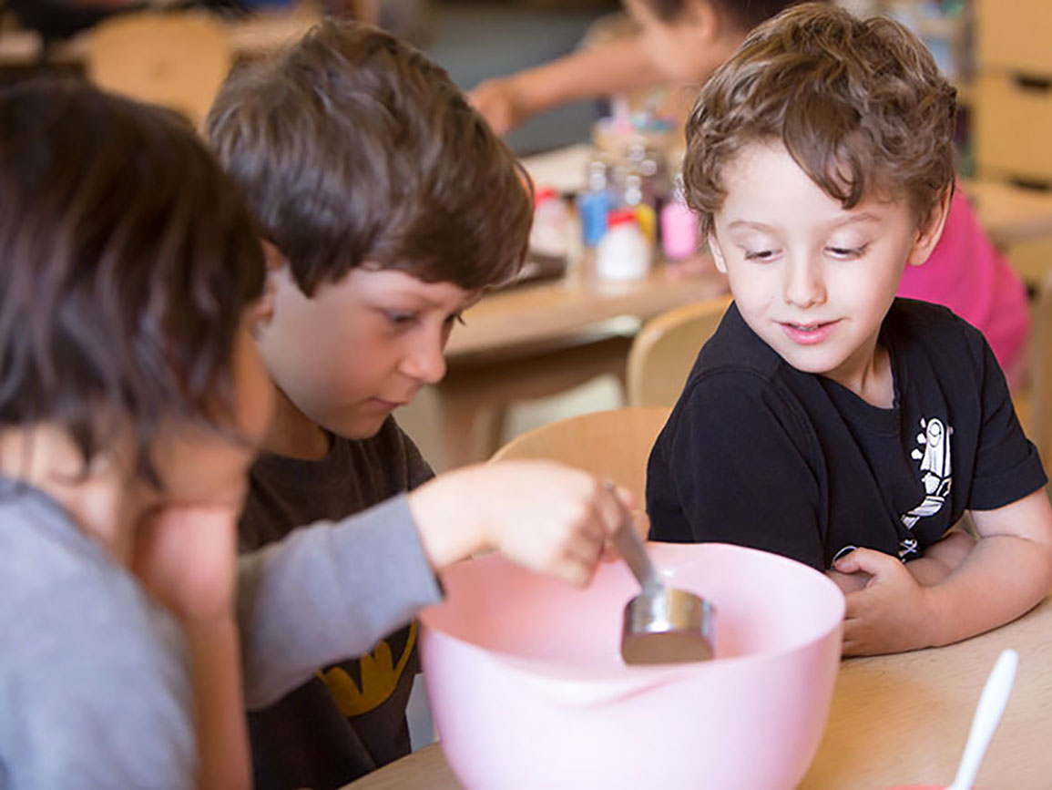 Three preschoolers using a measuring cup and mixing bowl