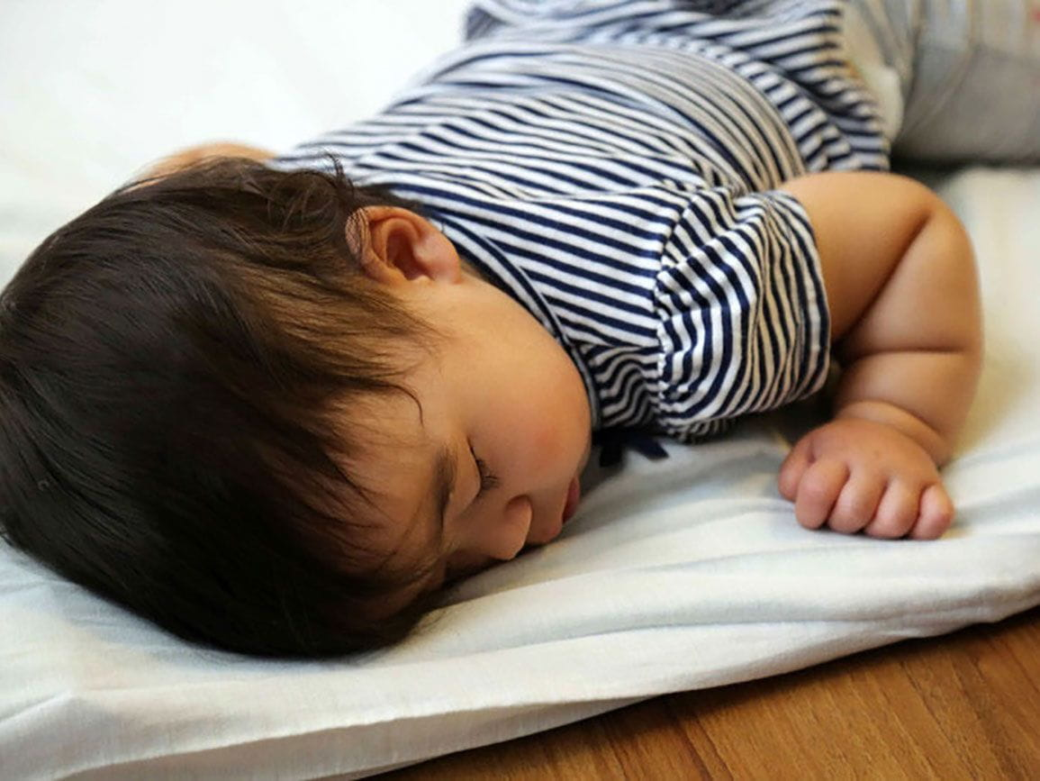 Toddler boy napping on a pad