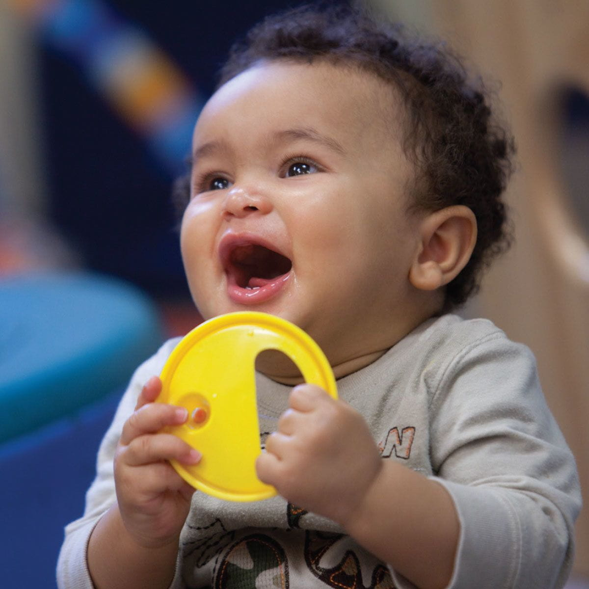 Infant boy holding a toy and smiling