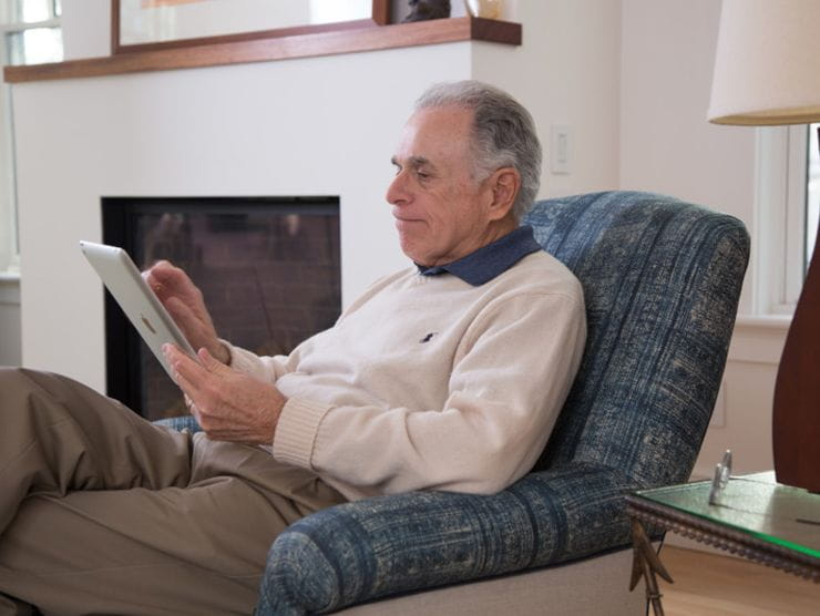 Elderly parent using a tablet to see his family