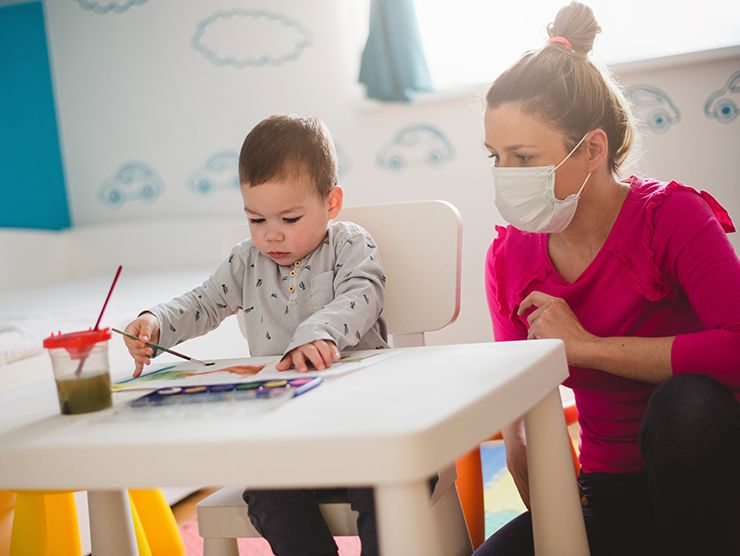 toddler doing an art project with a teacher in a mask