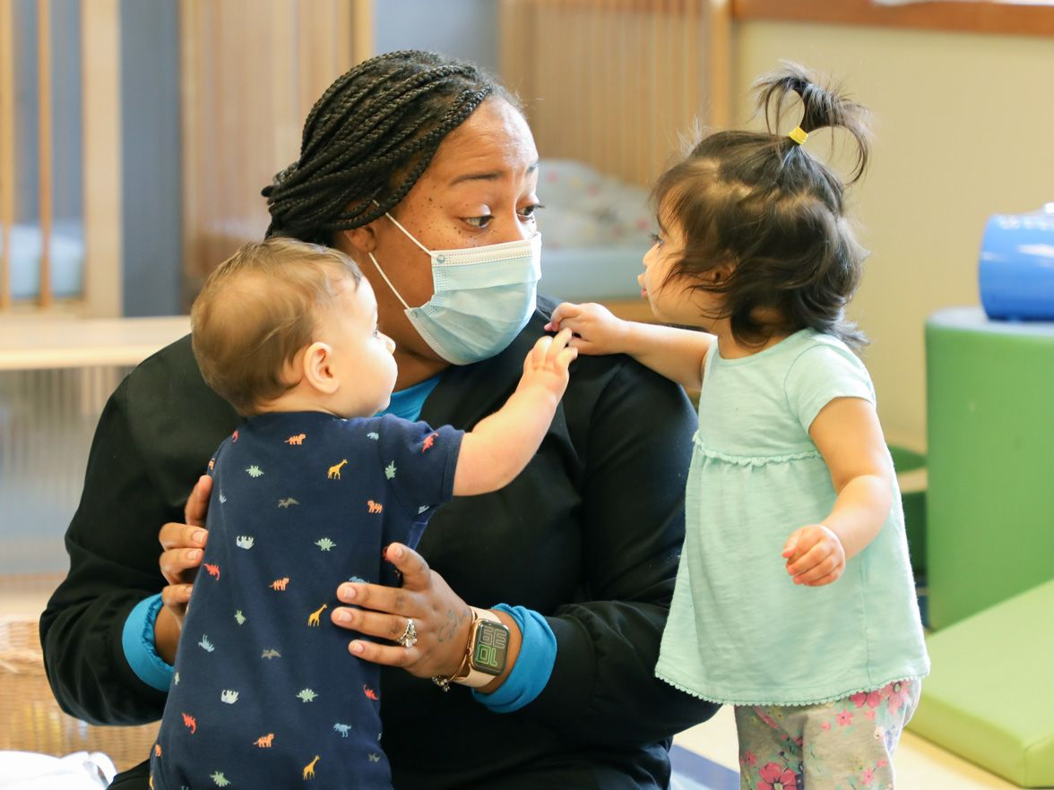 Teacher practicing safe health and safety wearing a mask, in front of two young children | Bright Horizons | Daycare