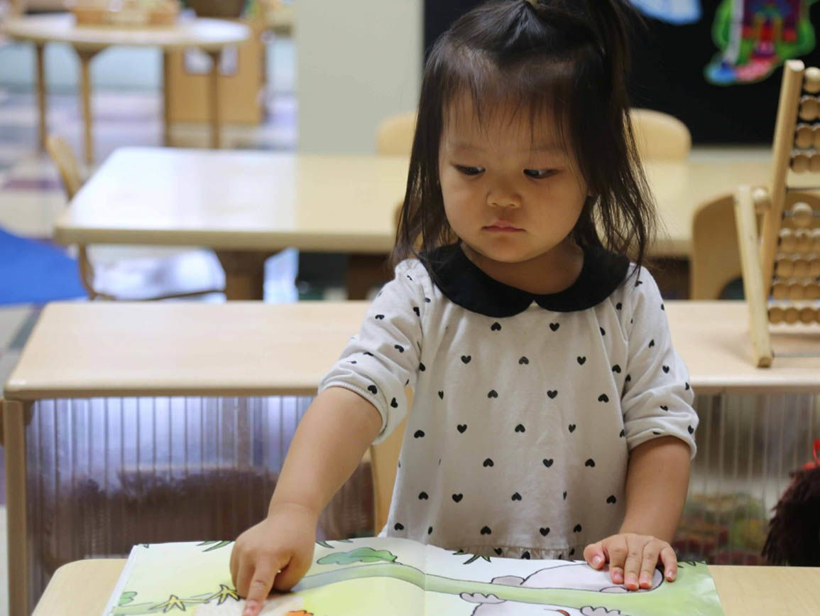 Preschool aged girl pointing to an open book on a desk
