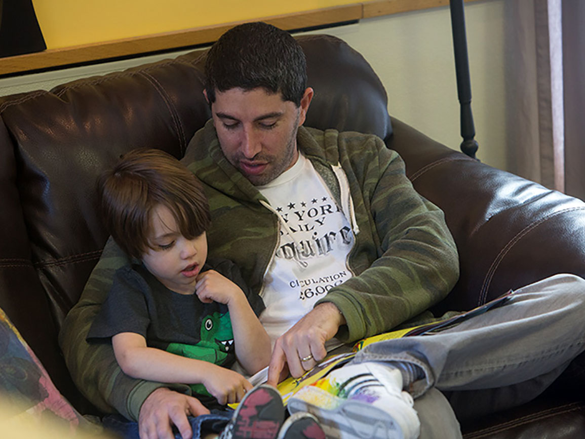 Father reading to his young son on a couch
