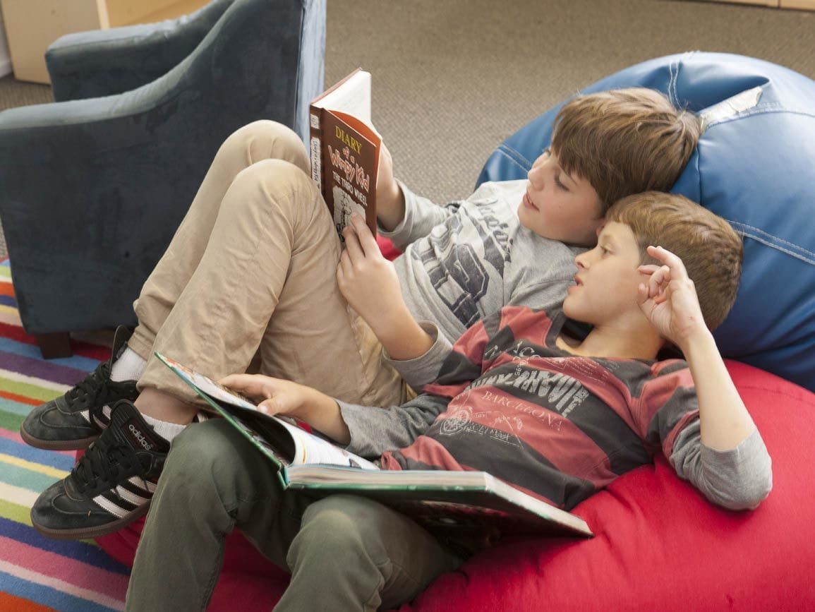 Two kindergarten boys on bean bags reading together