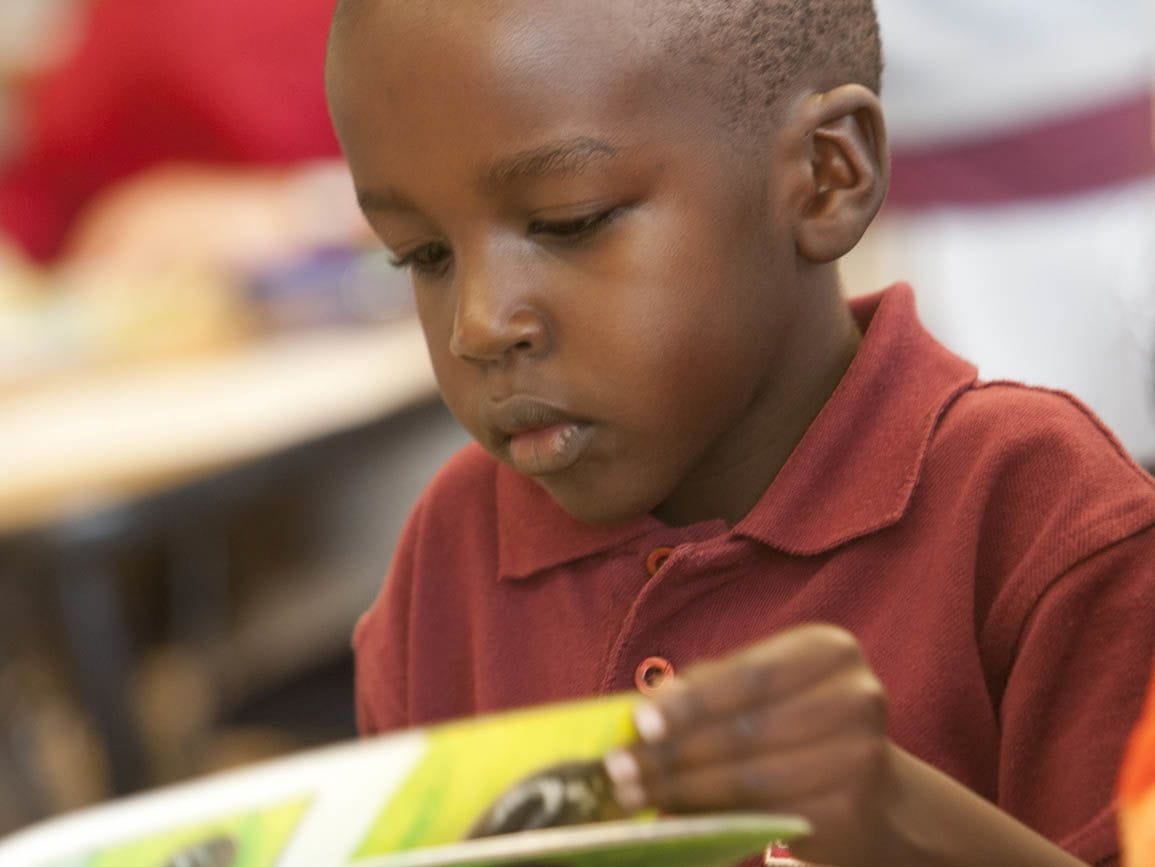 Pre-kindergarten boy sitting and reading a book