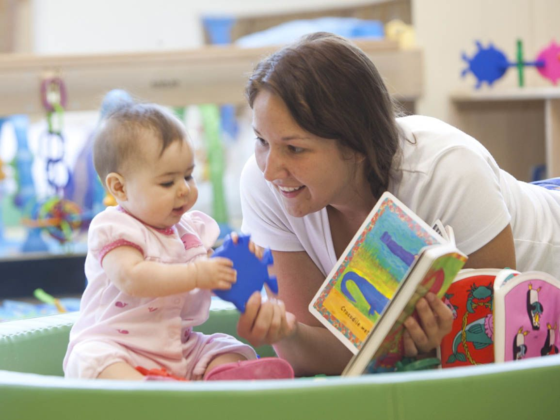 Teacher reading a book to an infant