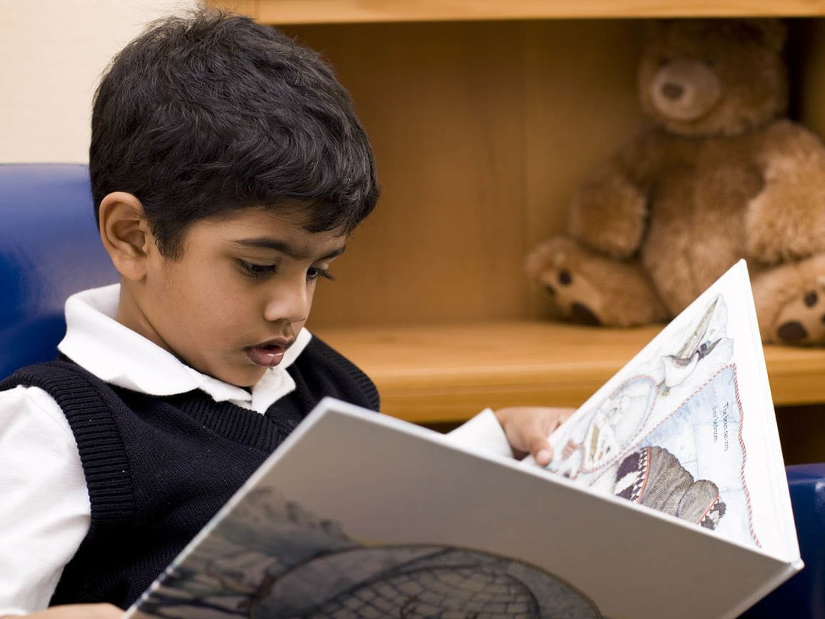 Preschool aged boy sitting and reading a book