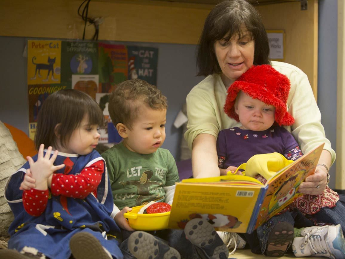 Teacher reading to three toddlers