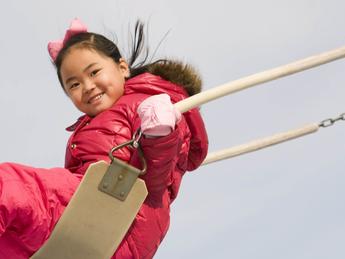 Young girl in a pink coat swinging