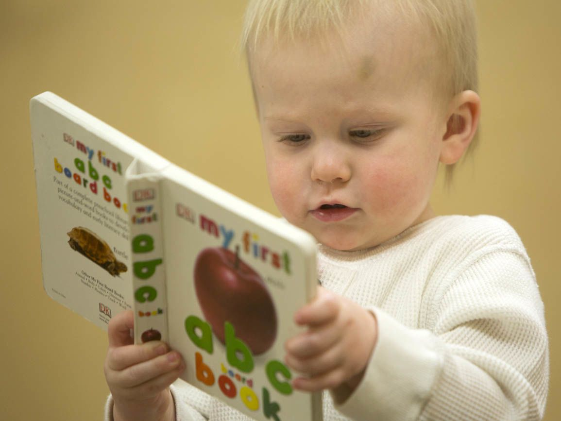 Infant holding a book