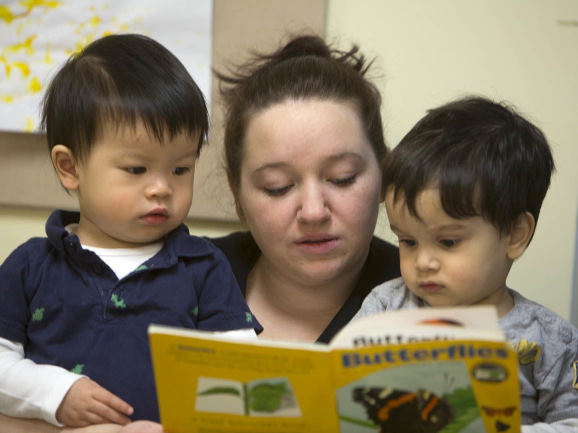 Teacher reading to two toddler boys