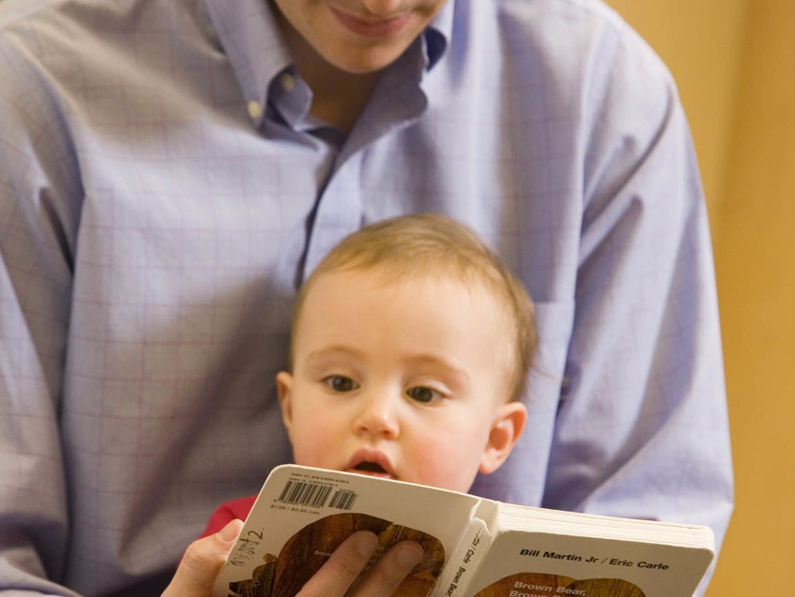 Dad reading to his infant son sitting in his lap