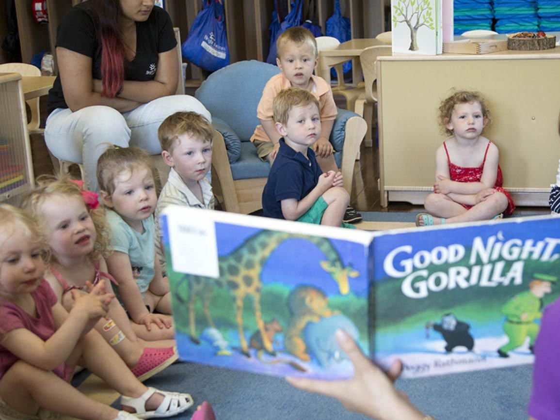 Co-ed group of toddlers sitting & listening to the teacher read aloud