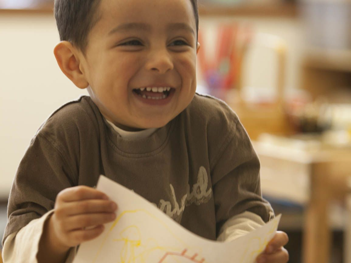 Preschool aged boy smiling and holding his drawing