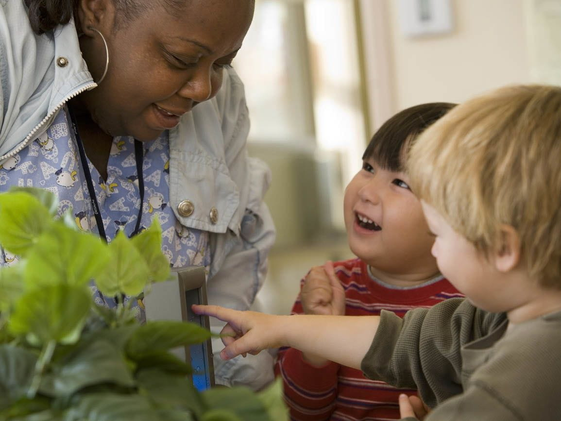 Teacher observing plants with two toddlers