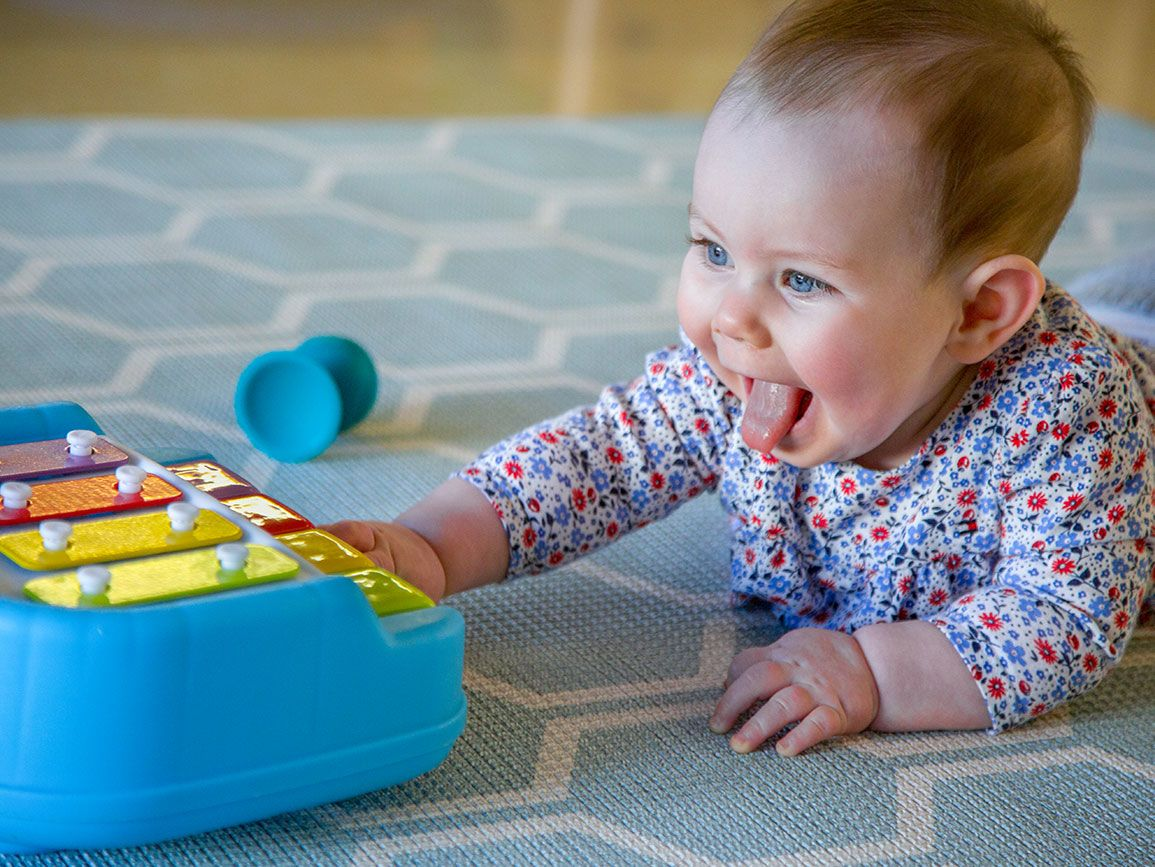 Infant girl on her tummy playing with a xylophone