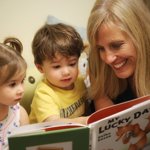 Teacher reading to a toddler boy and girl