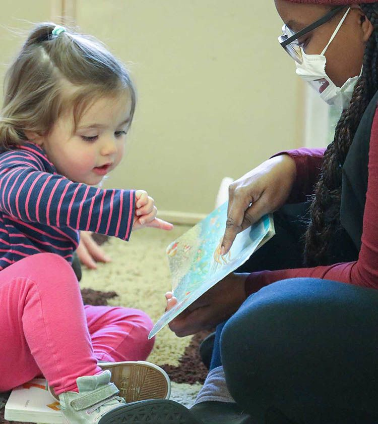 Teacher with transparent mask reads to toddler | Bright Horizons