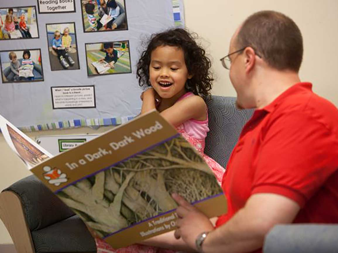 Kindergarten-aged girl reading with dad