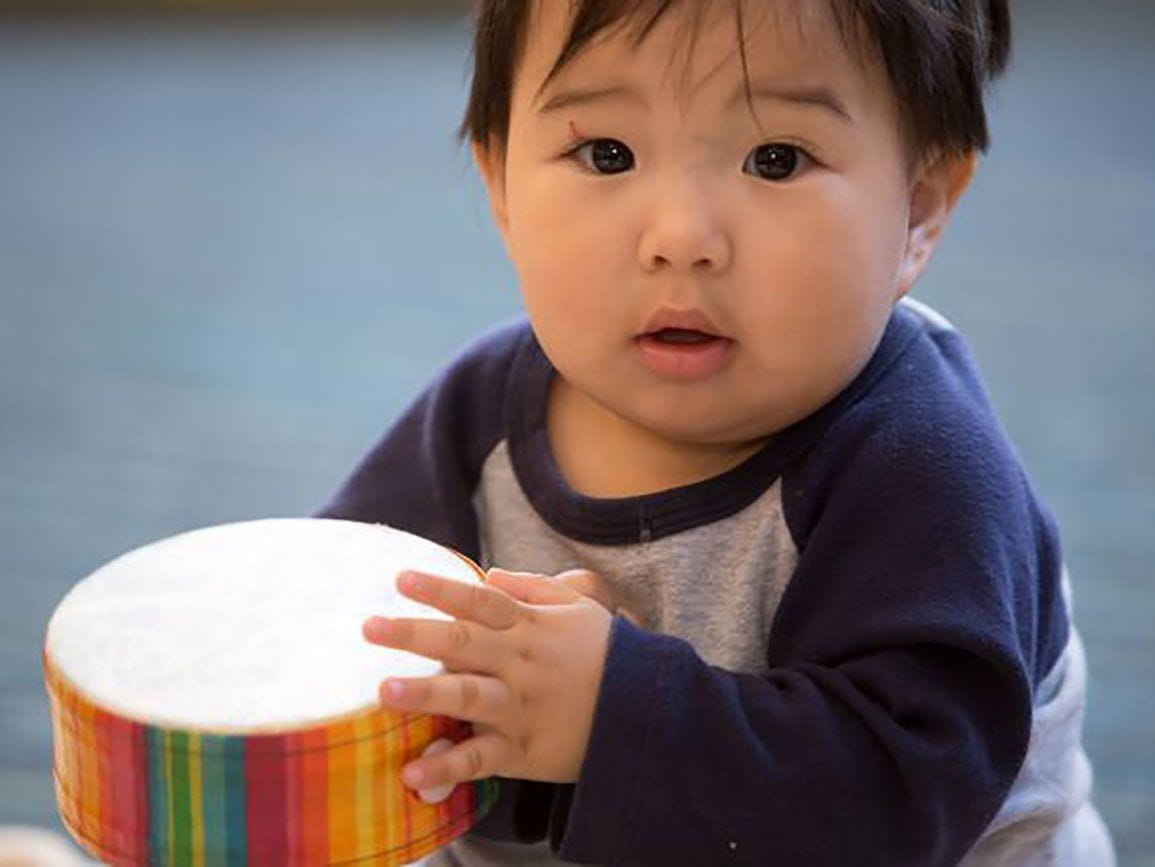 Baby playing a drum