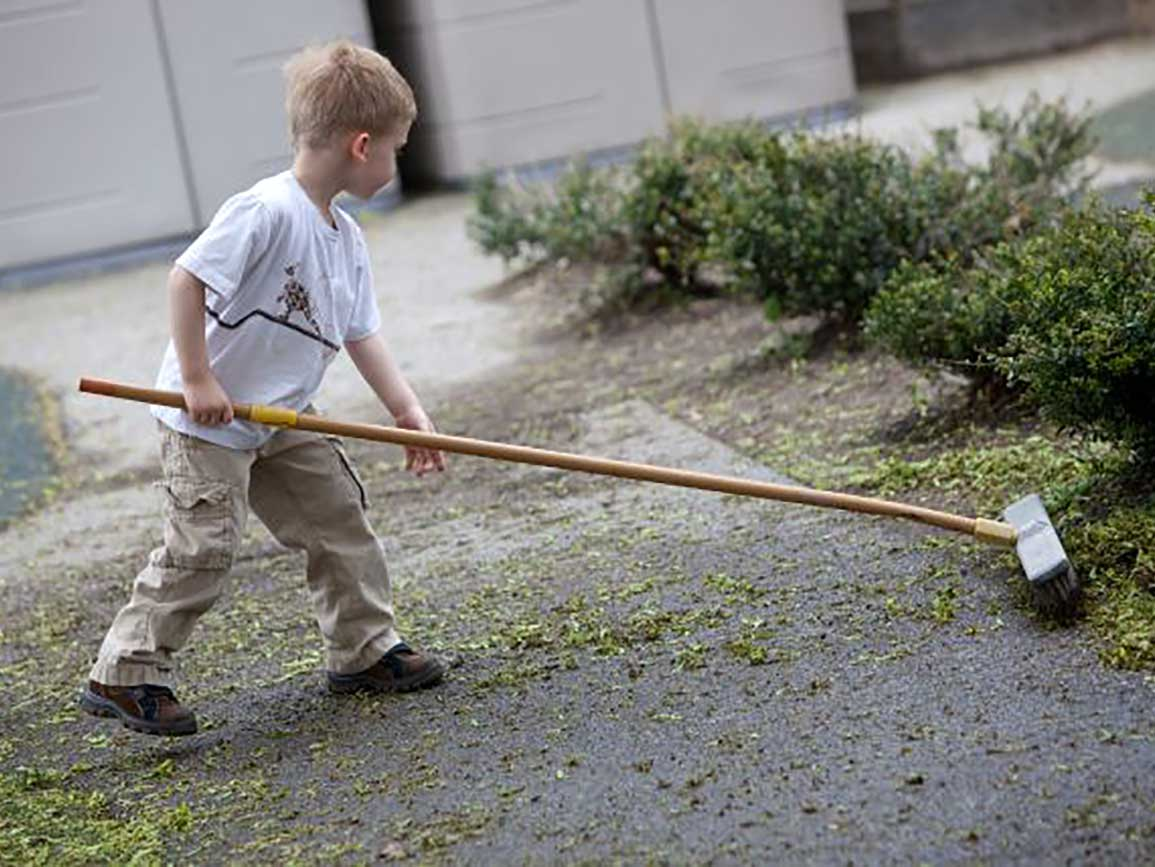Kindergarten boy sweeping outside